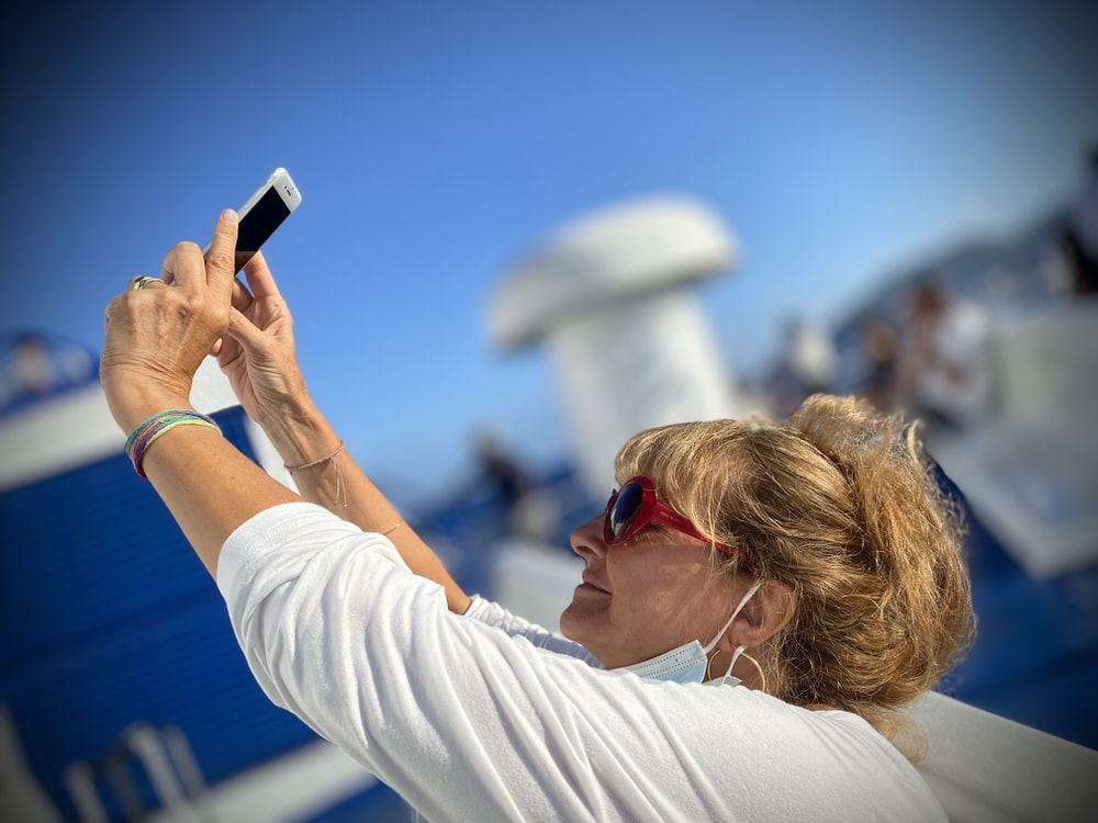 woman in white long sleeve shirt holding smartphone during daytime