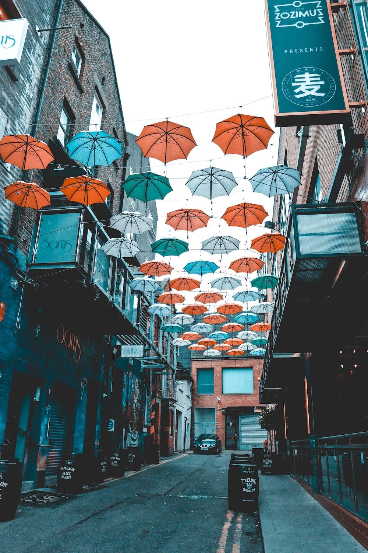 orange umbrella hanging on the street during daytime