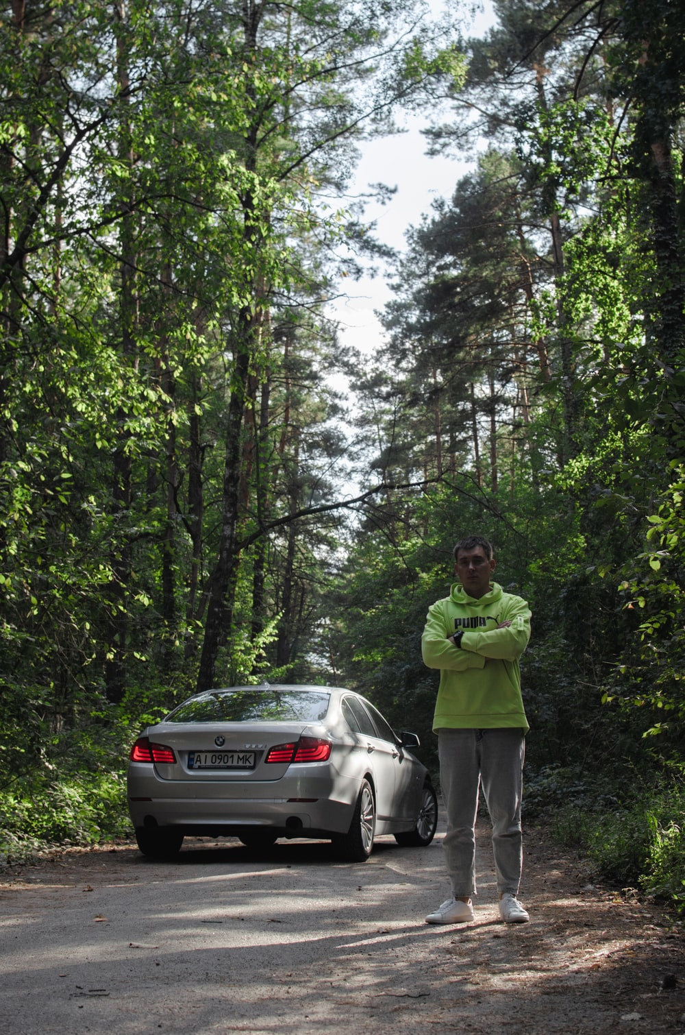 man in green jacket standing beside silver car