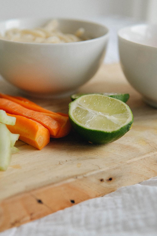 sliced lemon and green leaf on white ceramic bowl
