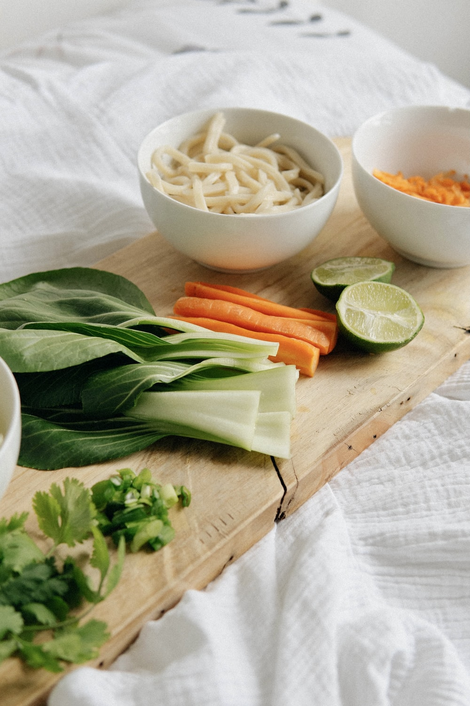 sliced carrots and green leaves on white ceramic bowl