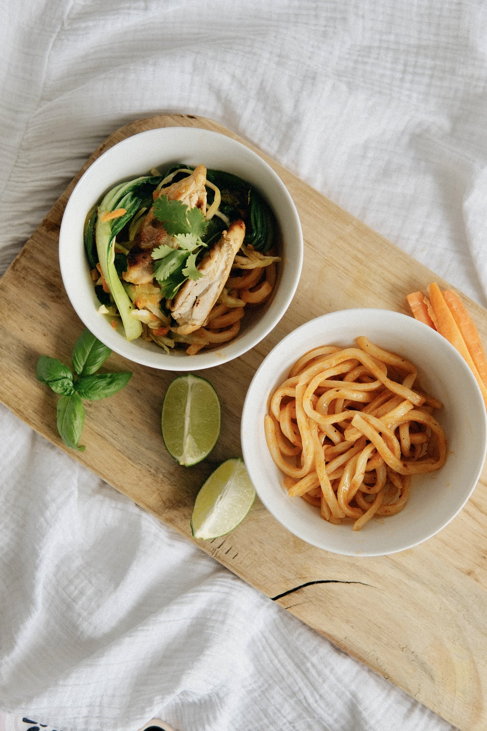 white ceramic bowl with white pasta and green leaf