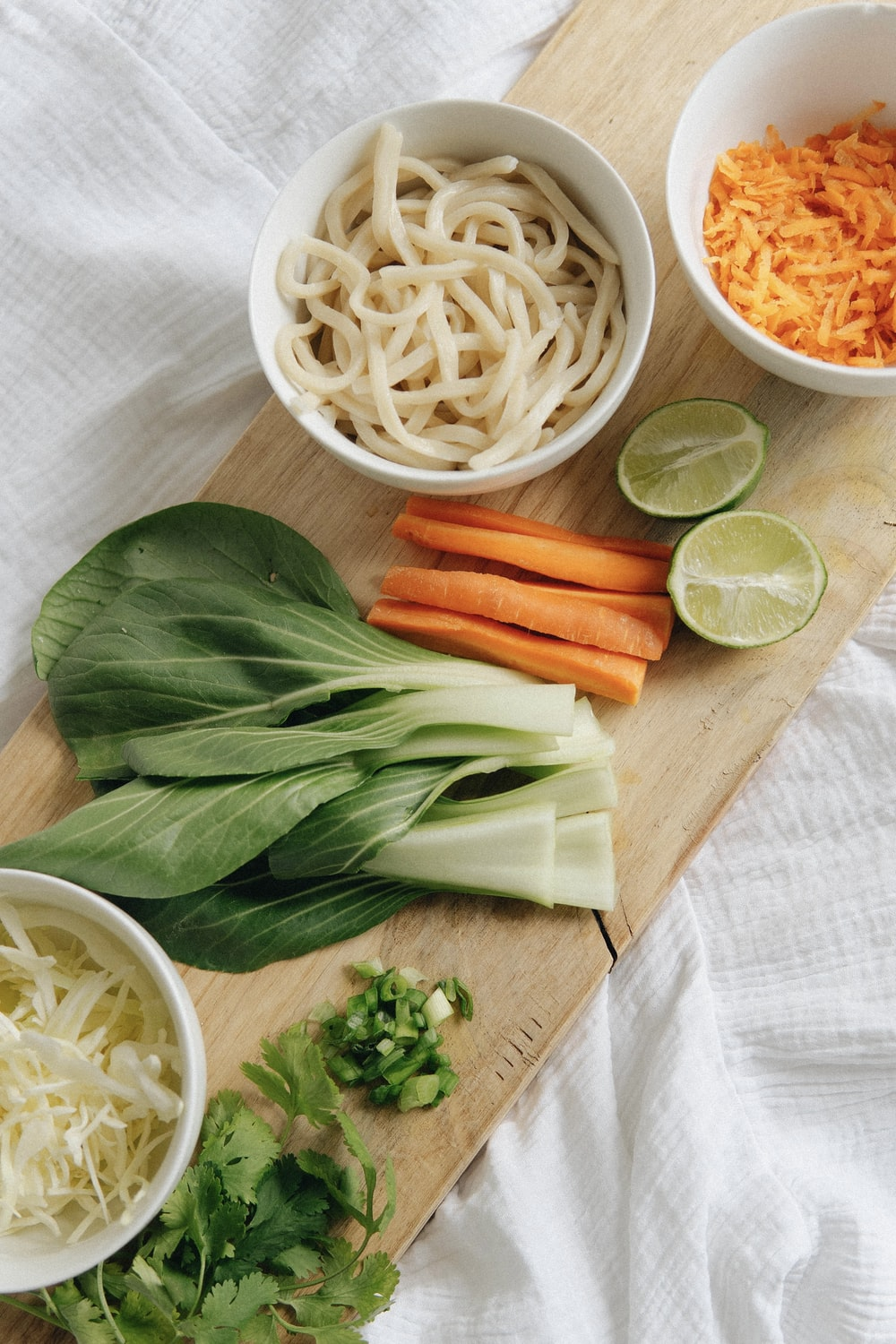 white pasta with carrots and green leaf vegetable on brown wooden chopping board