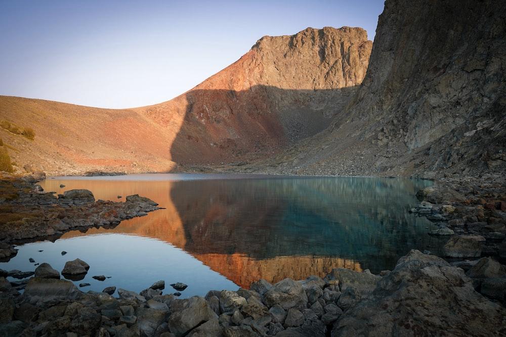 brown mountain near lake during daytime