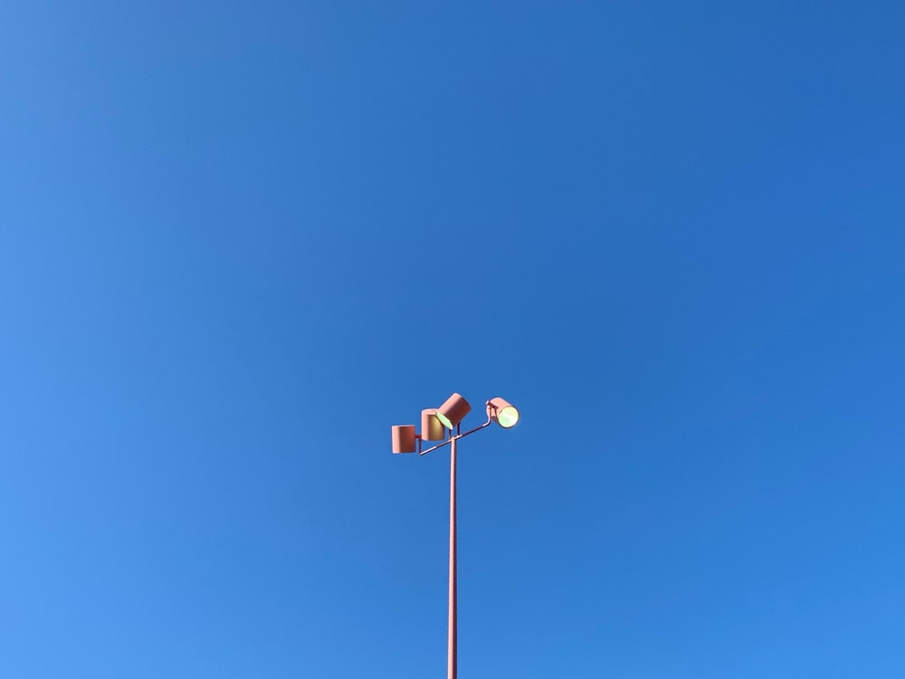 red and white street light under blue sky during daytime
