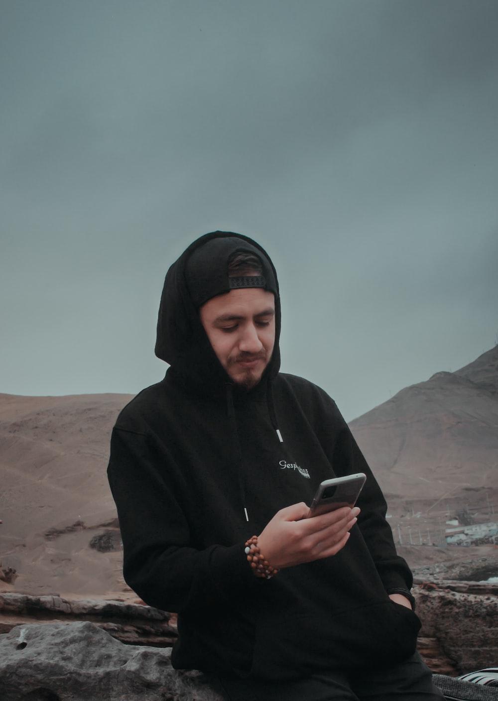 man in black hoodie holding smartphone