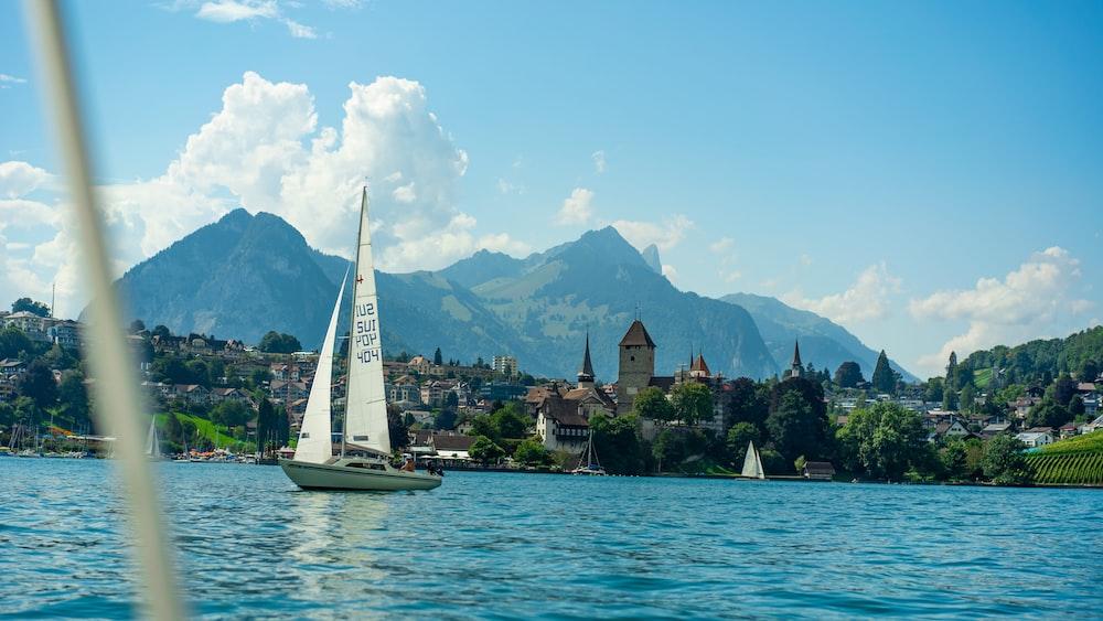 white sailboat on water near green mountains during daytime