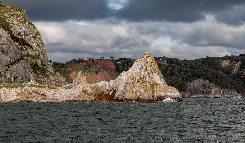brown rock formation on sea under gray clouds