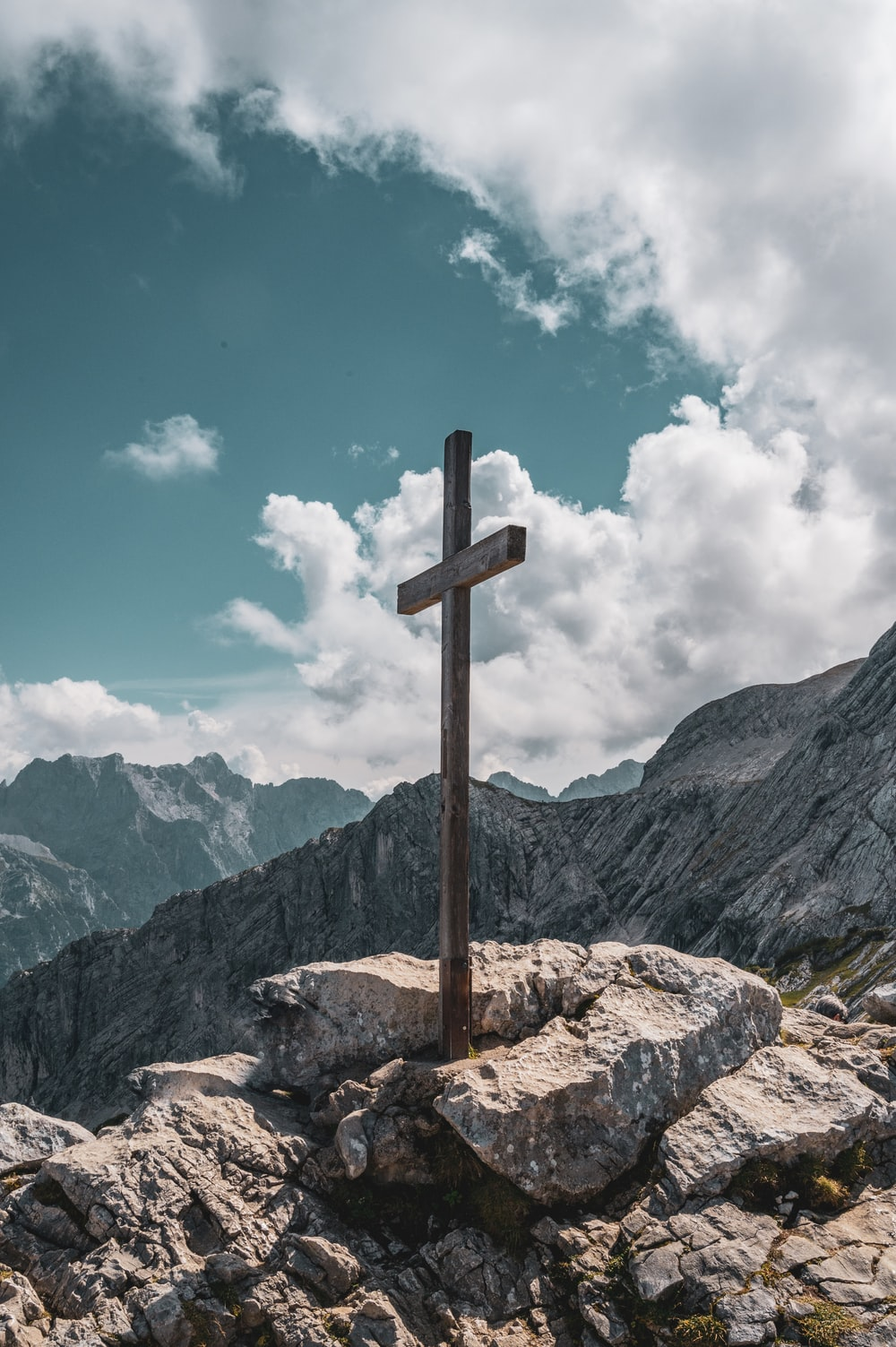brown wooden cross on brown rock near green mountains under blue sky and white clouds during