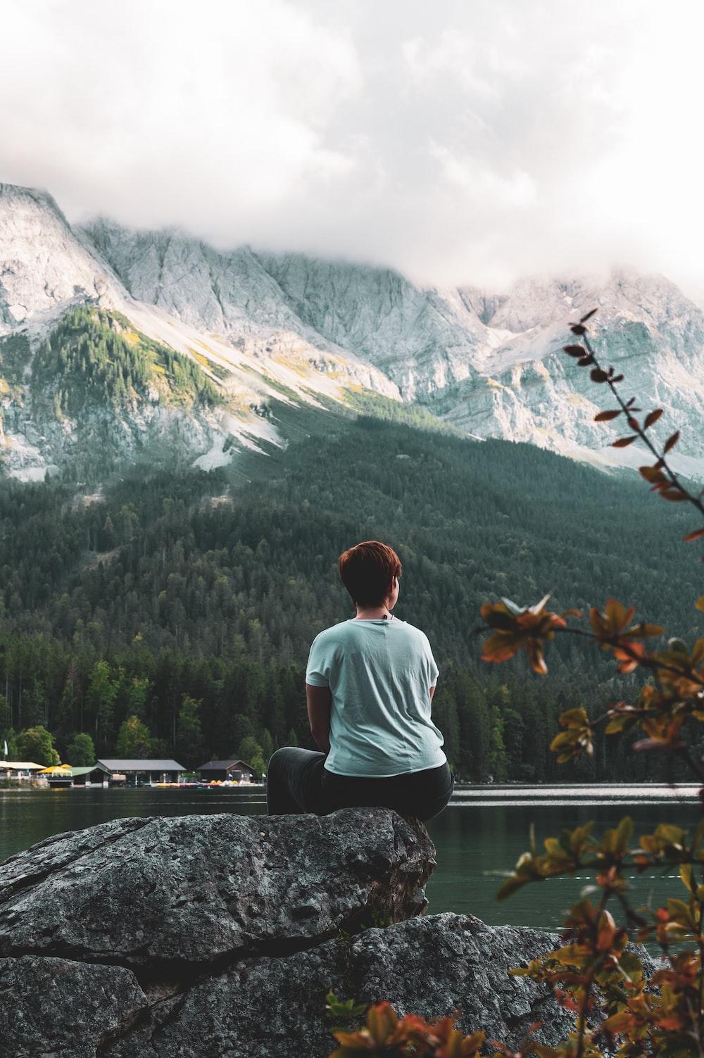 man in white shirt sitting on rock near lake and mountains during daytime