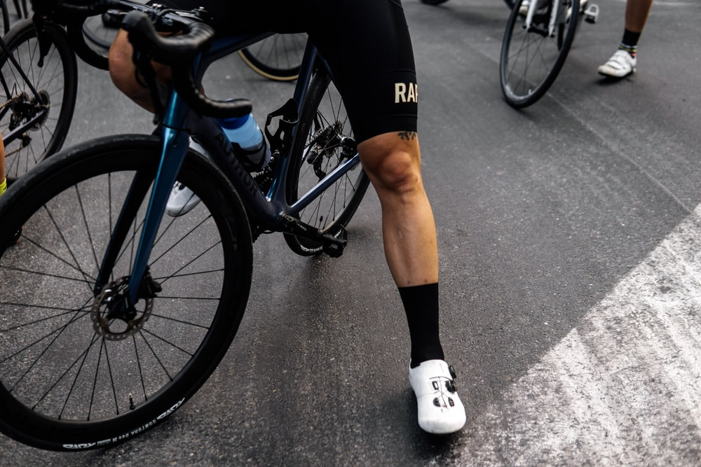 person in black shorts and white socks riding blue and black mountain bike