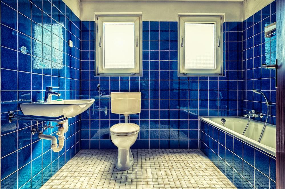 white ceramic sink beside blue wall tiles