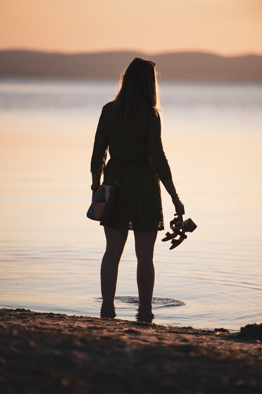 woman in black coat standing on beach during sunset
