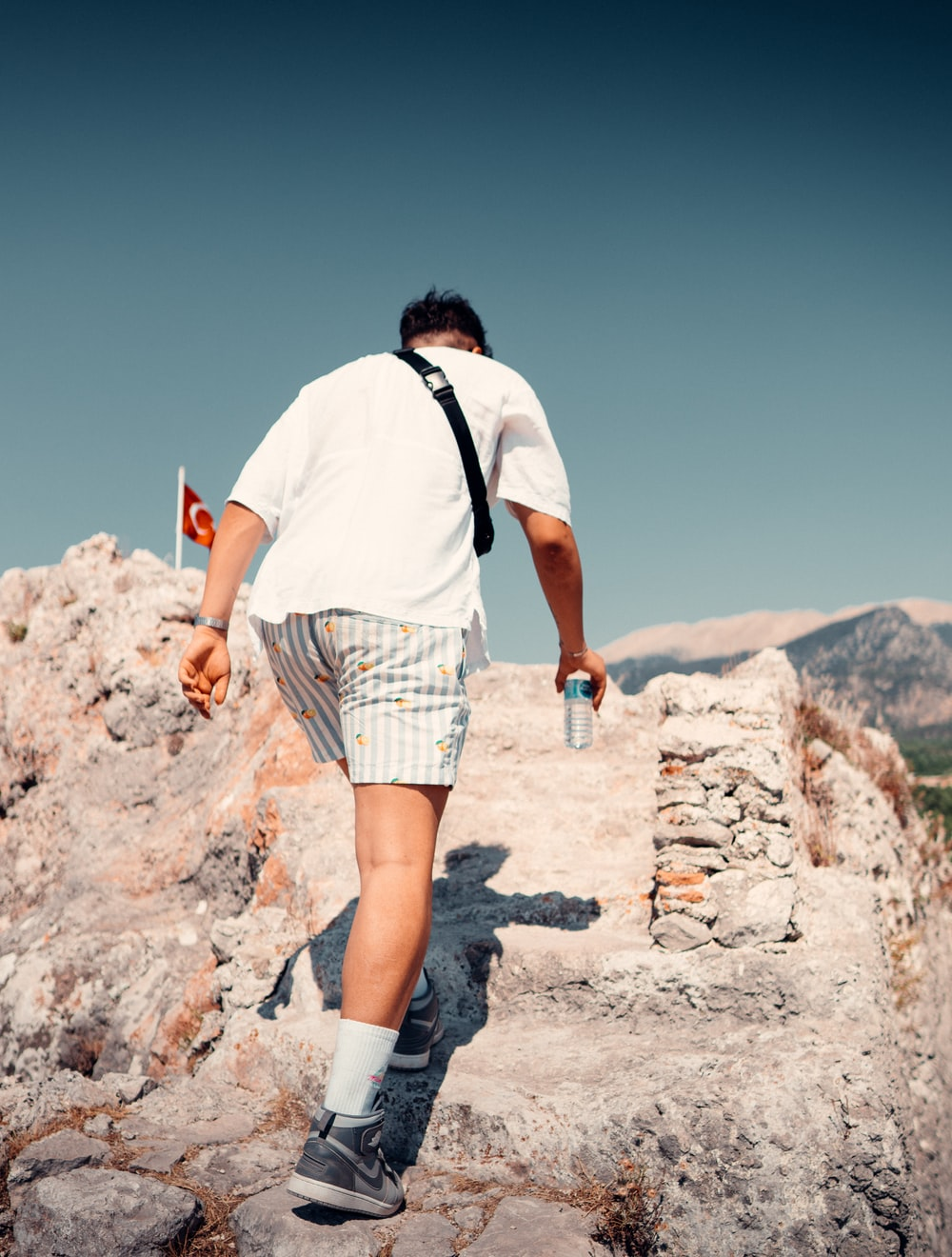 man in white t-shirt and brown plaid shorts standing on rocky hill during daytime