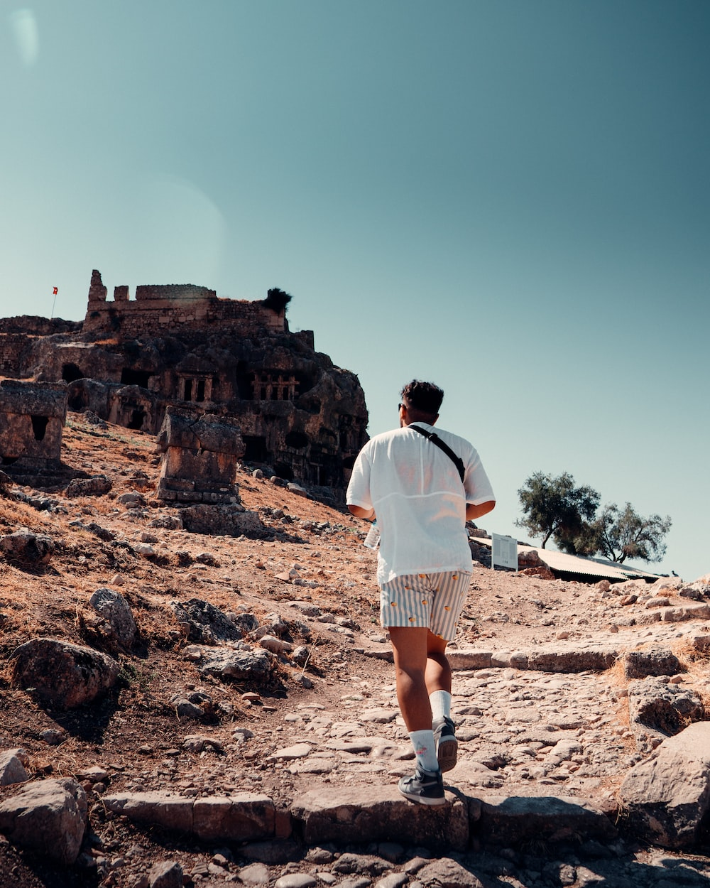 man in white shirt and white shorts standing on brown rock formation during daytime