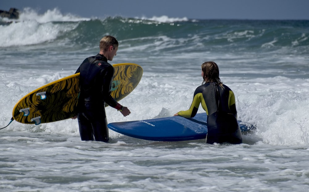 man in black wet suit holding blue surfboard on beach during daytime