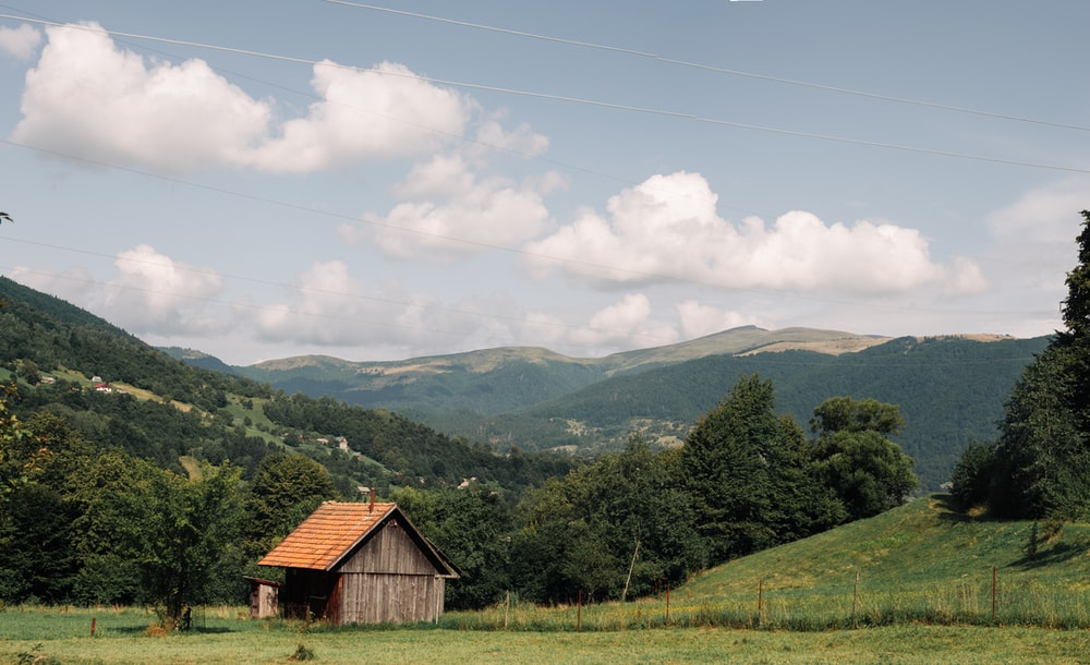 brown wooden house on green grass field near green mountains under white clouds and blue sky