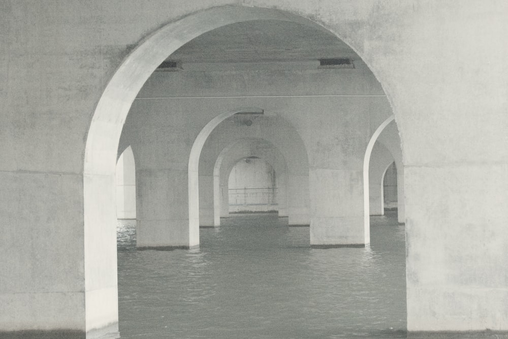 gray concrete arch on body of water