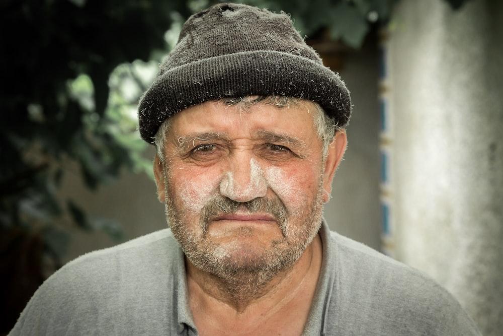man in gray shirt wearing black knit cap