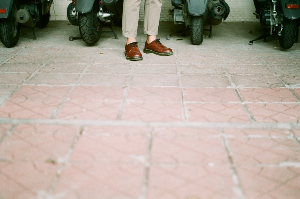 person in white pants and brown leather shoes