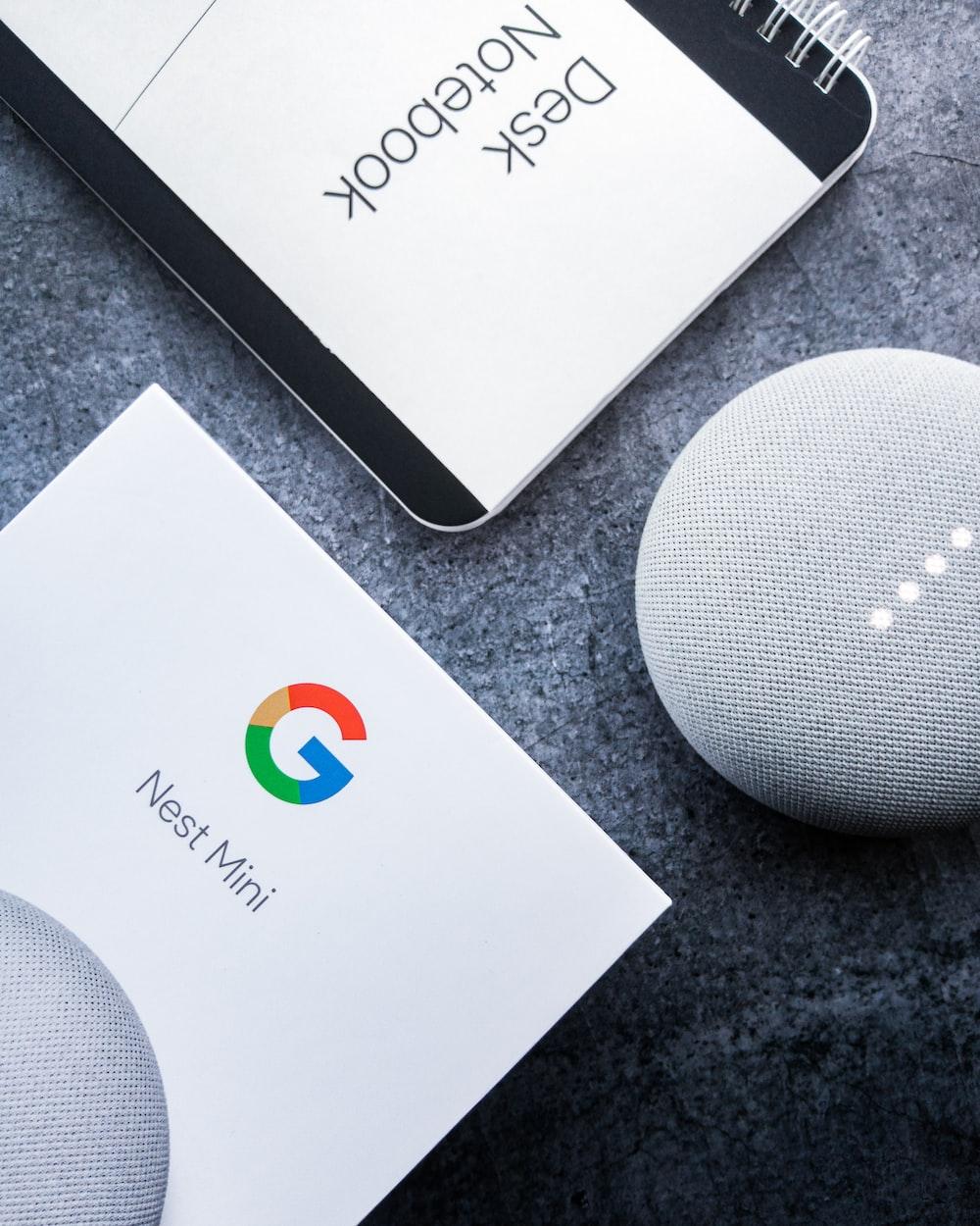 white google home mini on black table