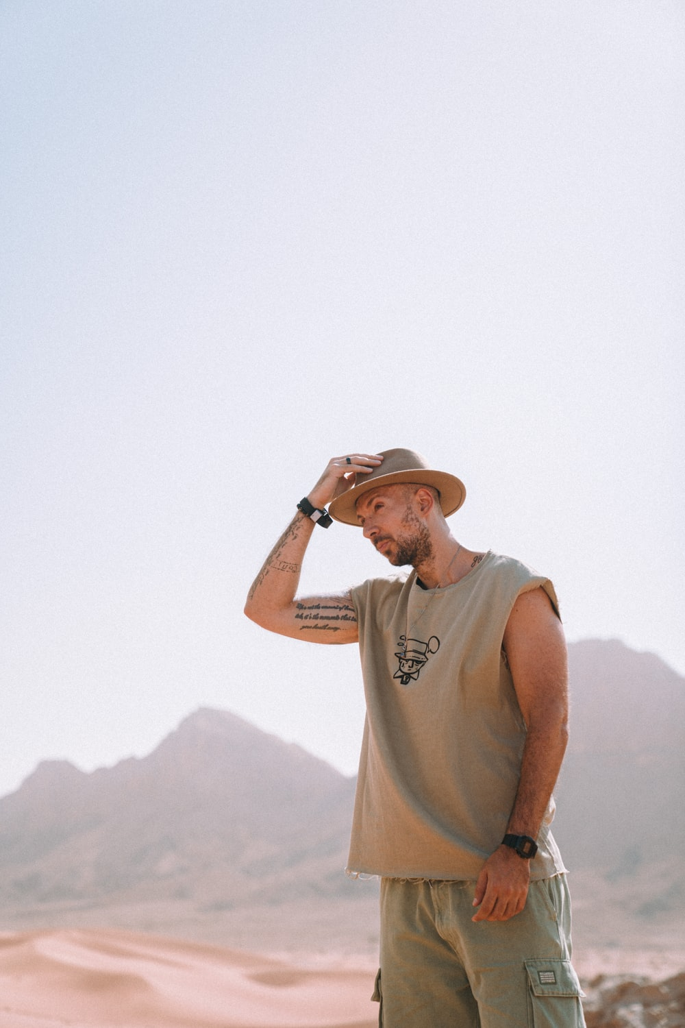 man in gray tank top and brown hat standing on top of mountain during daytime