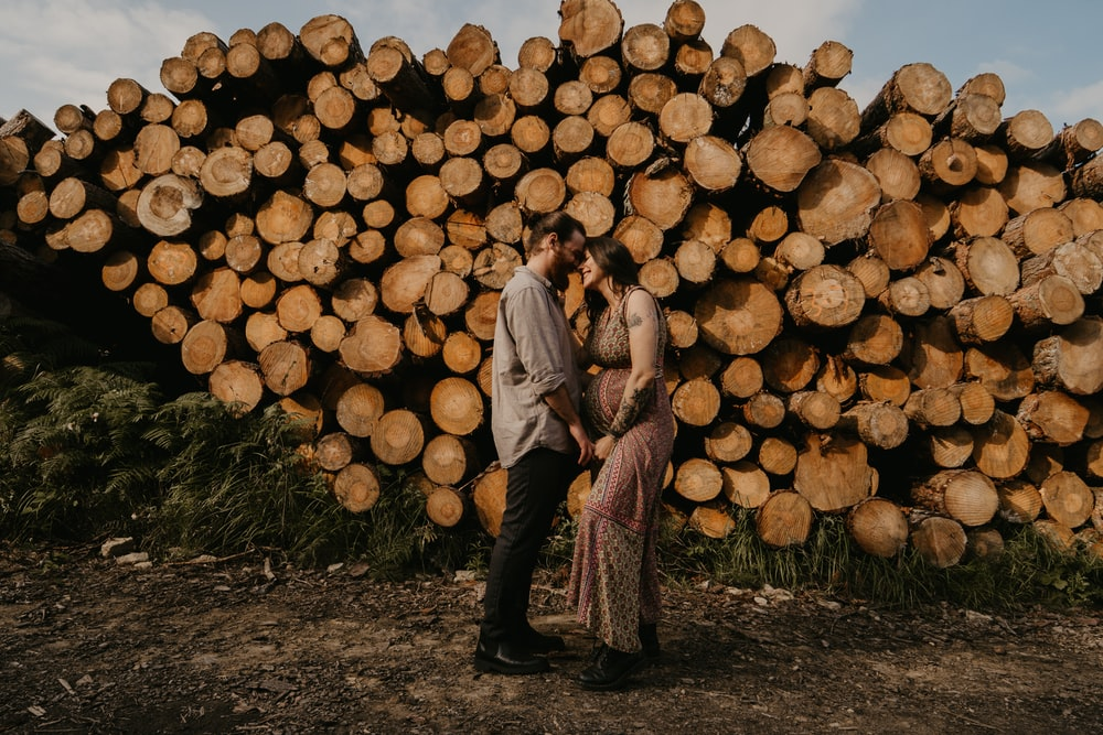 man and woman standing beside brown wood logs