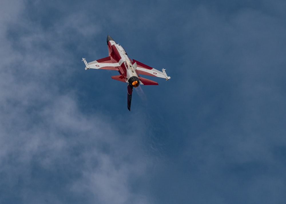 red and white airplane flying in the sky