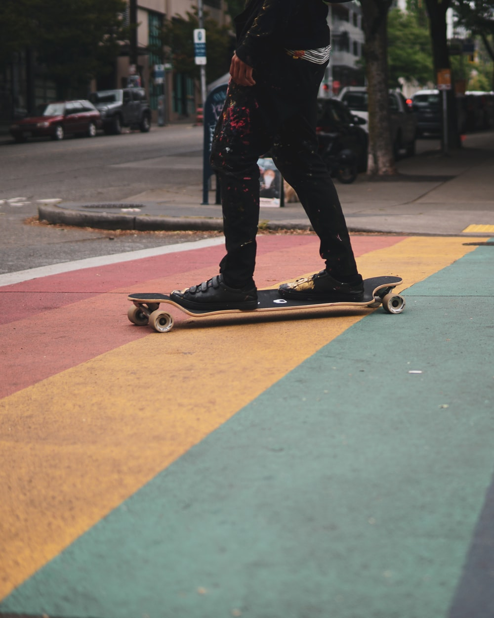 man in black pants and black shoes riding on skateboard during daytime