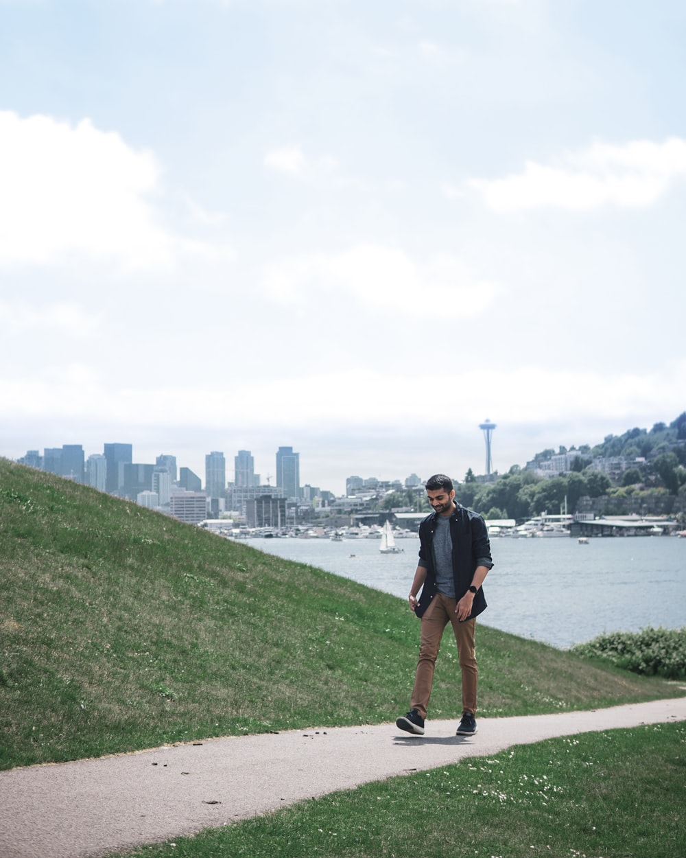man in black t-shirt and black shorts standing on gray concrete pavement near body of near near near near