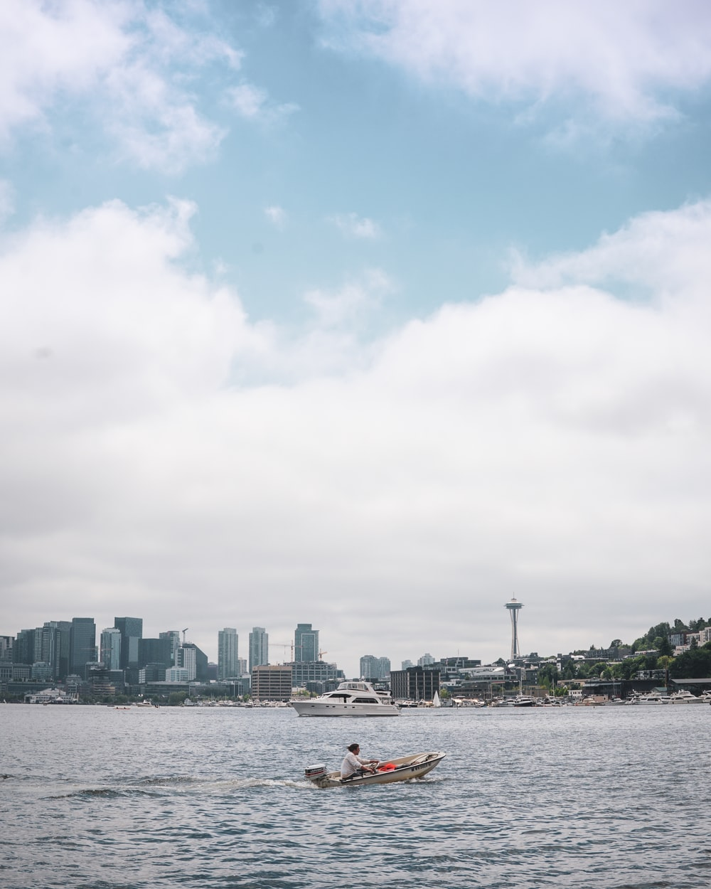 people riding on boat on sea near city buildings during daytime