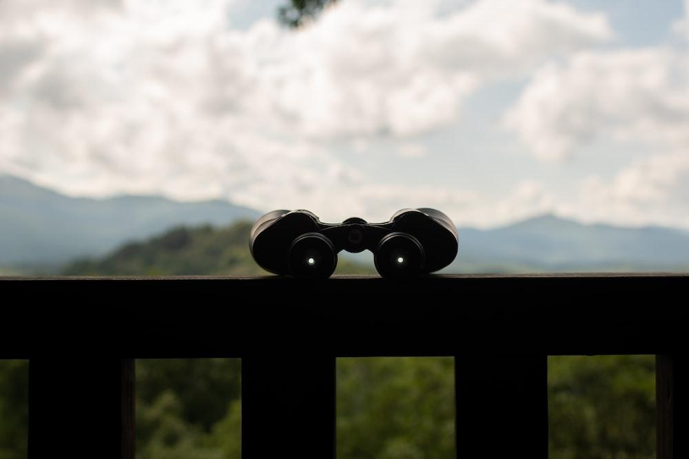 black binoculars on black metal bar during daytime