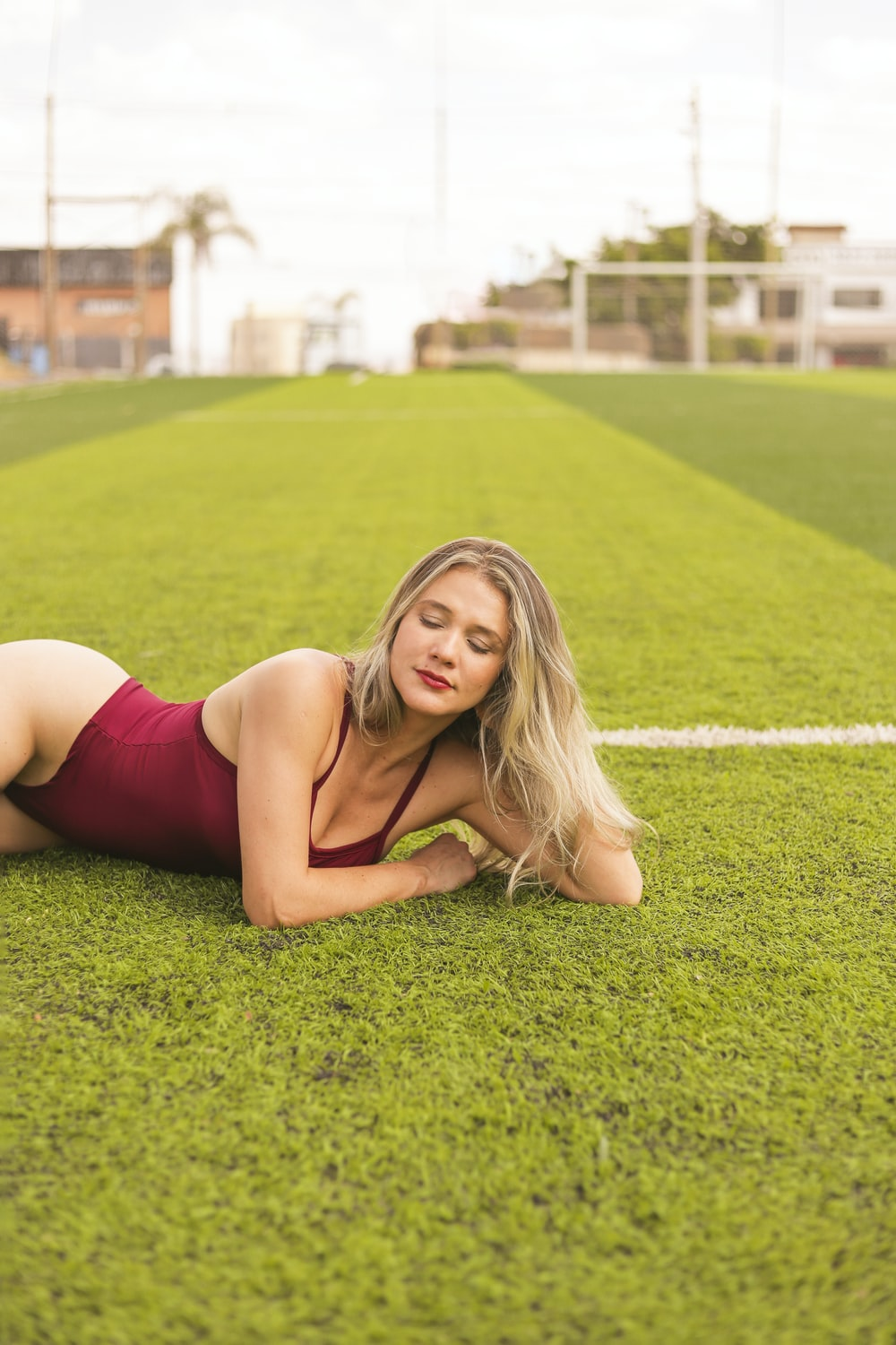 woman in red tank top lying on green grass field during daytime