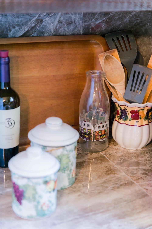 clear glass bottle beside white ceramic bowl