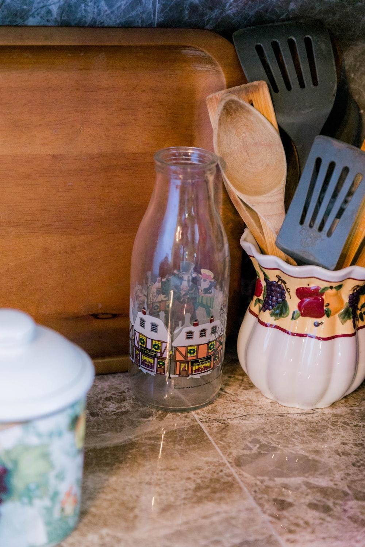 white ceramic vase beside clear glass bottle