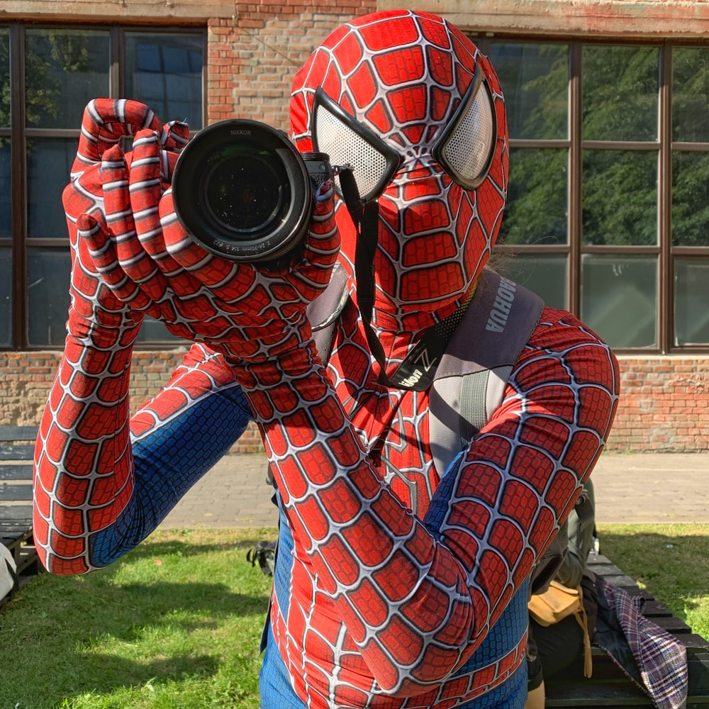 person in spider man costume holding black camera