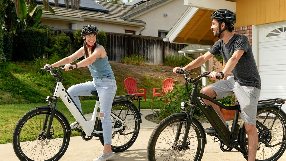 woman in gray tank top and white pants riding on orange and black bicycle during daytime