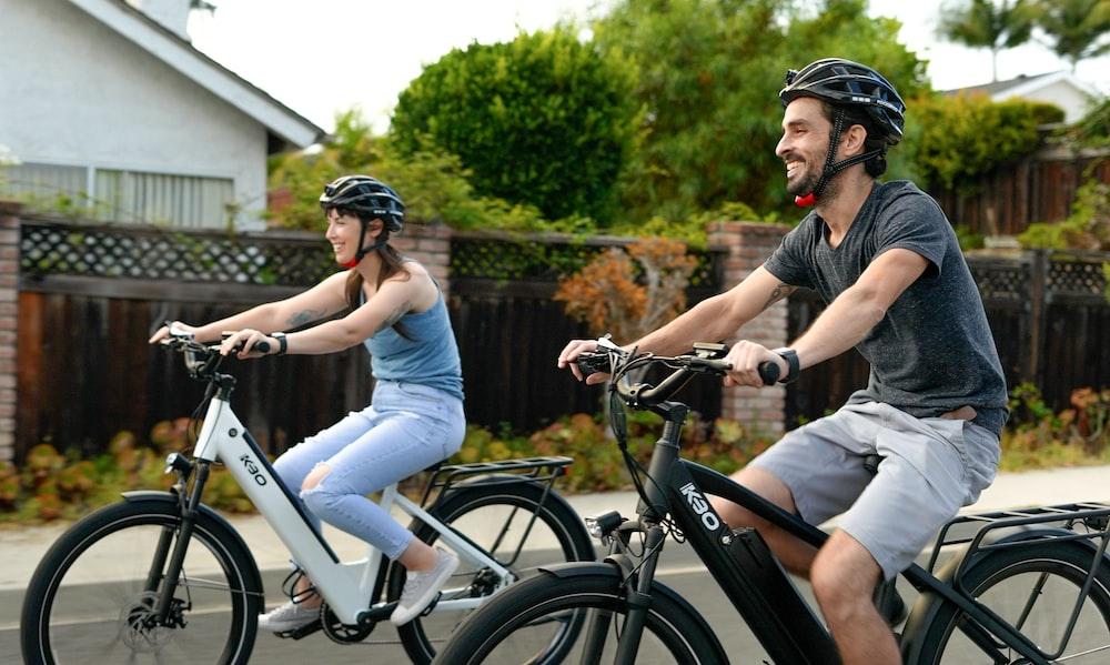 man in black t-shirt riding white bicycle
