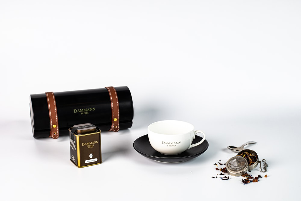 white ceramic teacup on saucer beside gold and black box mod