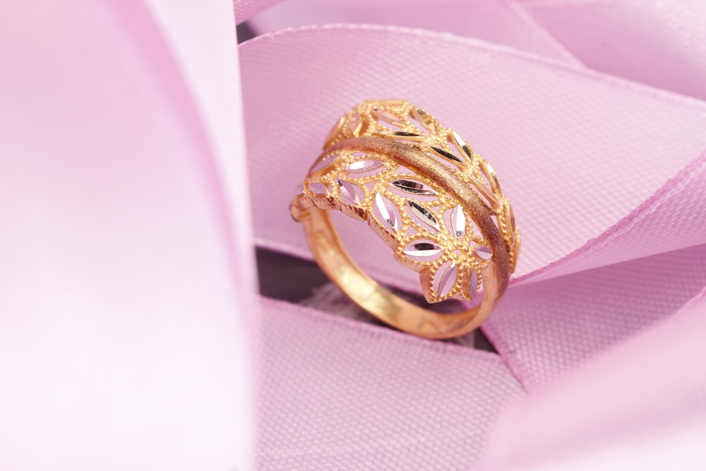 gold ring on pink textile