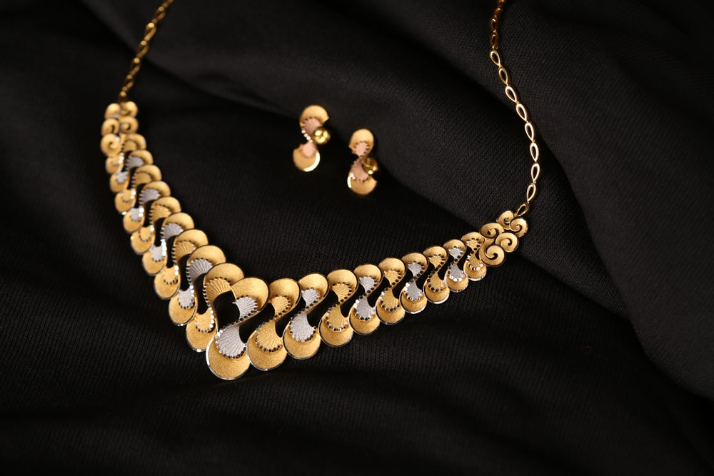 white pearl necklace on black textile