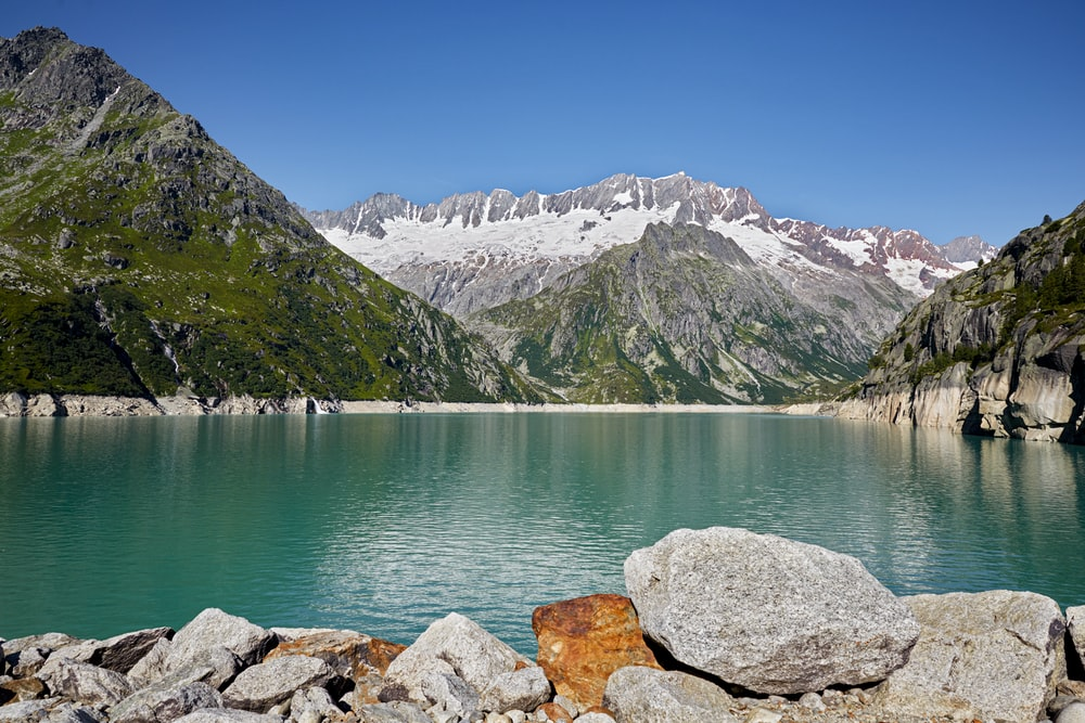 white and brown rocky mountain beside body of water during daytime
