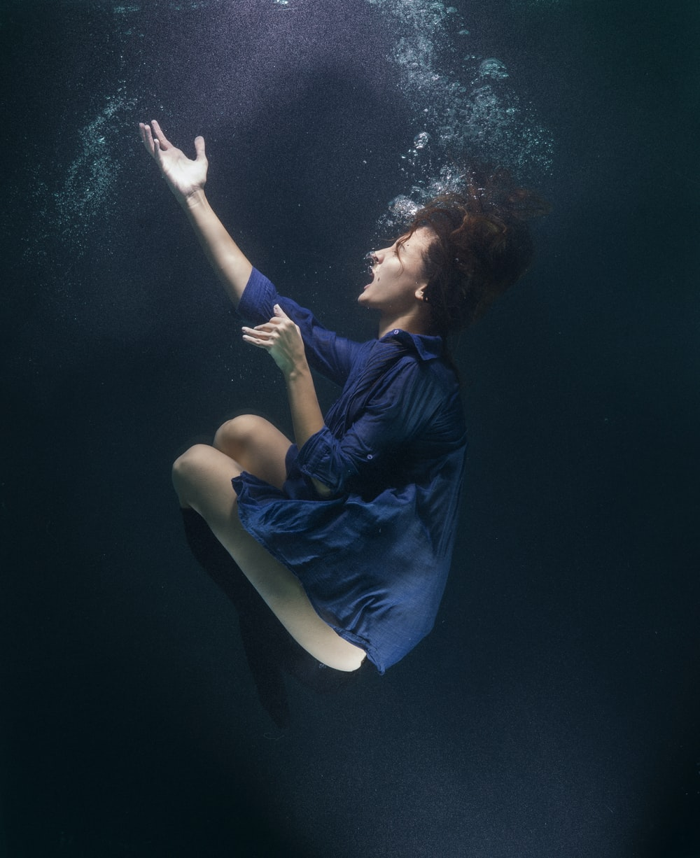 woman in blue shirt and white pants lying on blue water