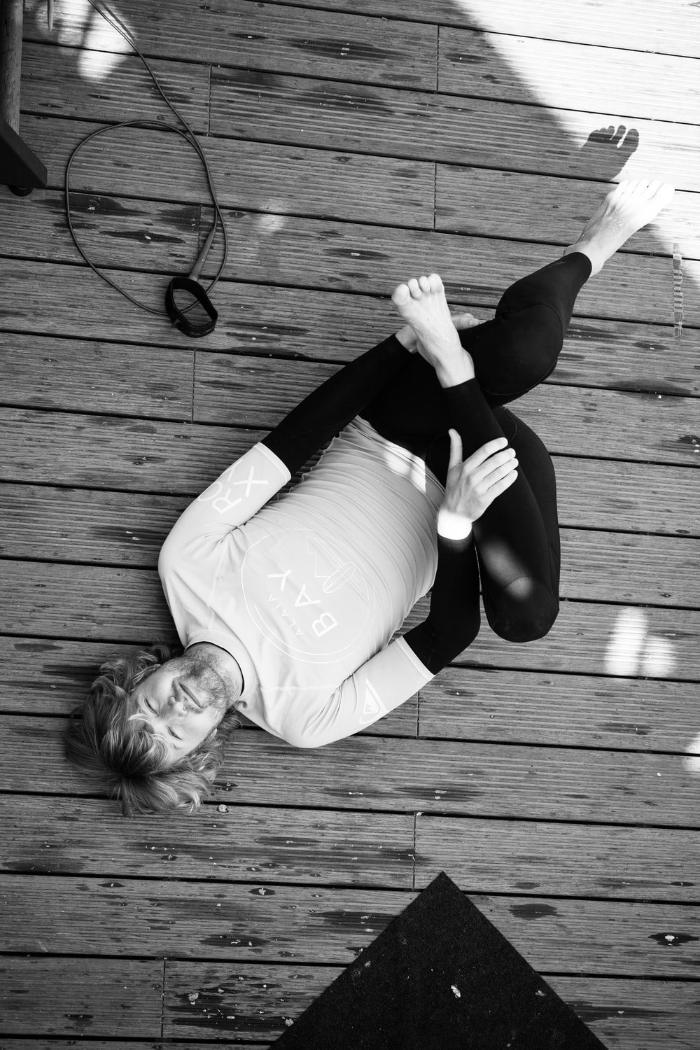 woman in white long sleeve shirt and black pants sitting on wooden floor