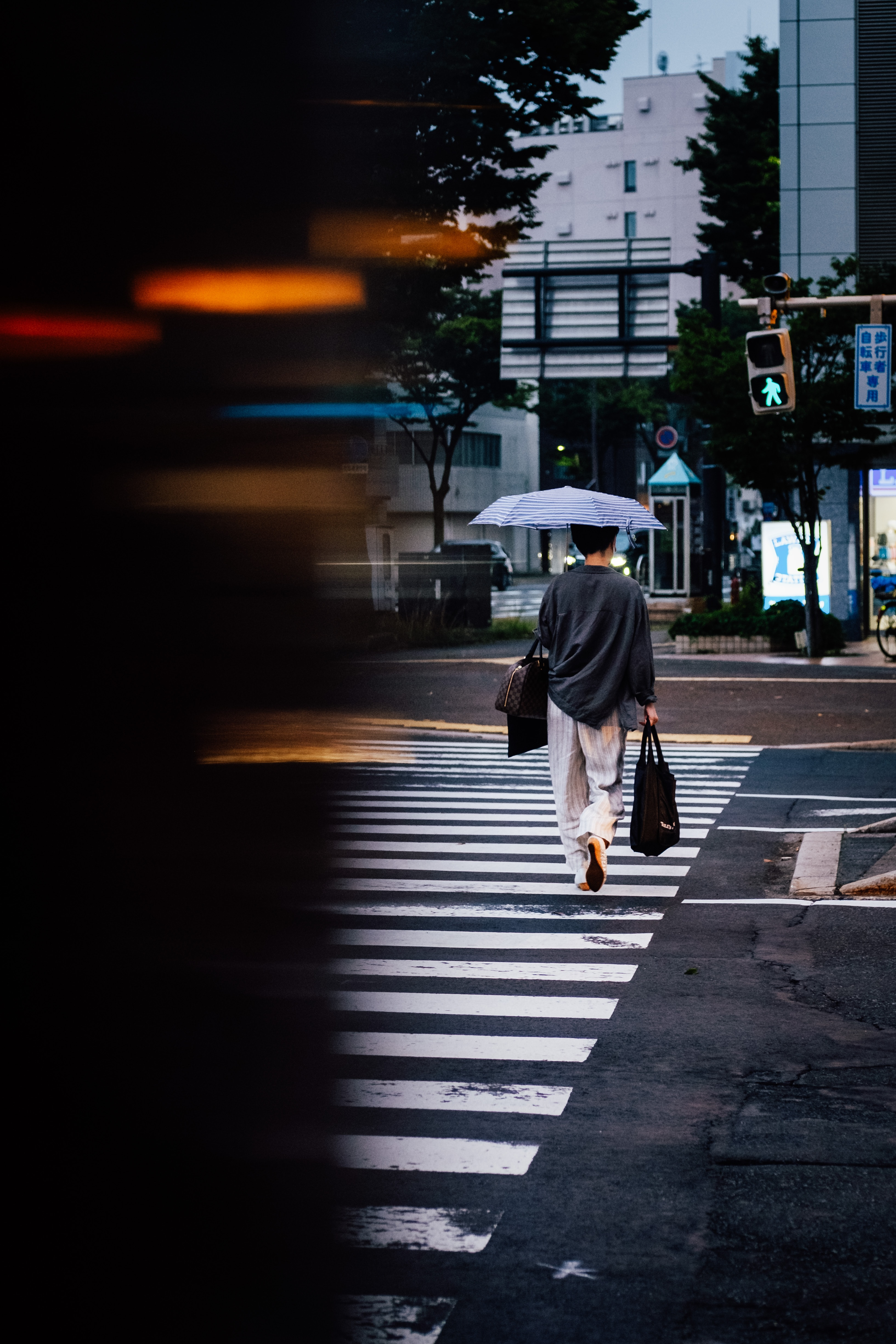 woman with umbrella crossing a street