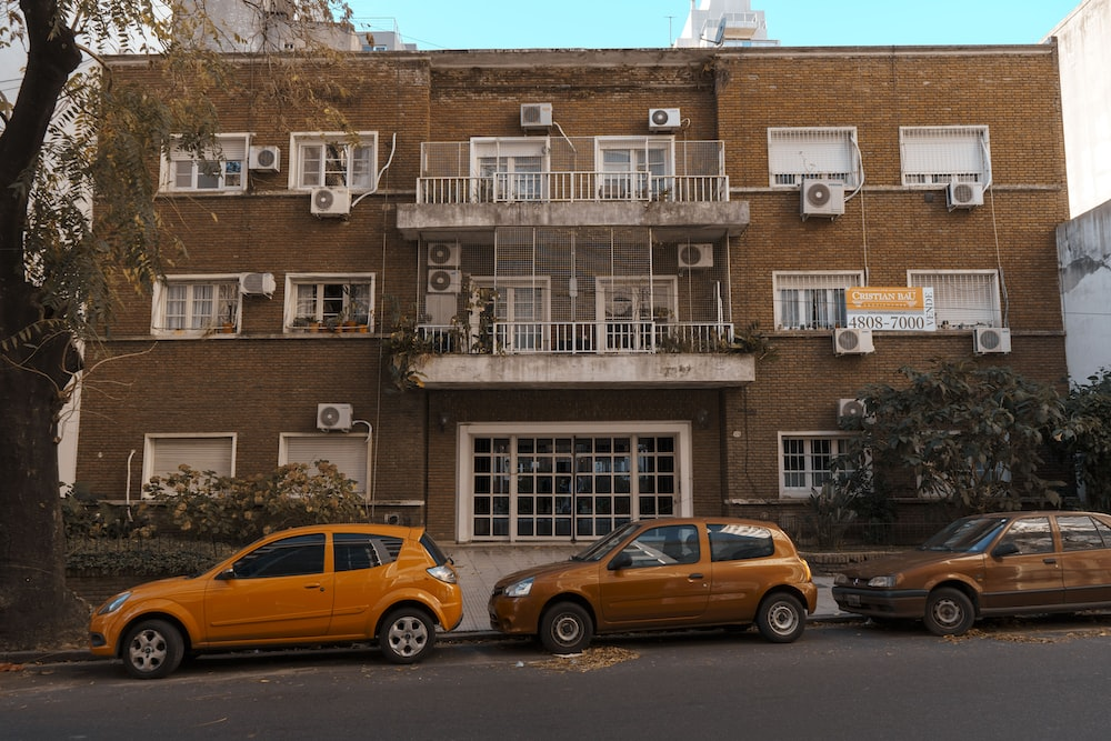 yellow 5 door hatchback parked beside brown concrete building during daytime