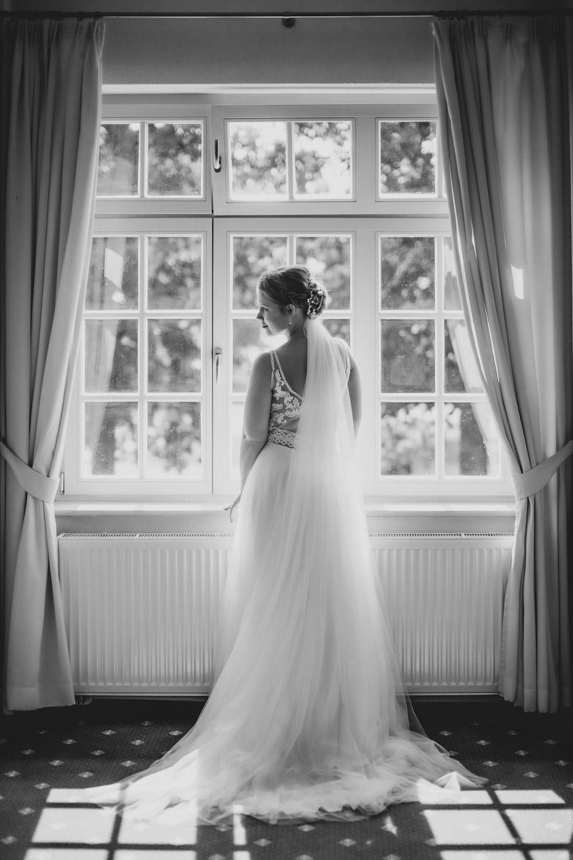 grayscale photo of woman in wedding dress standing beside window