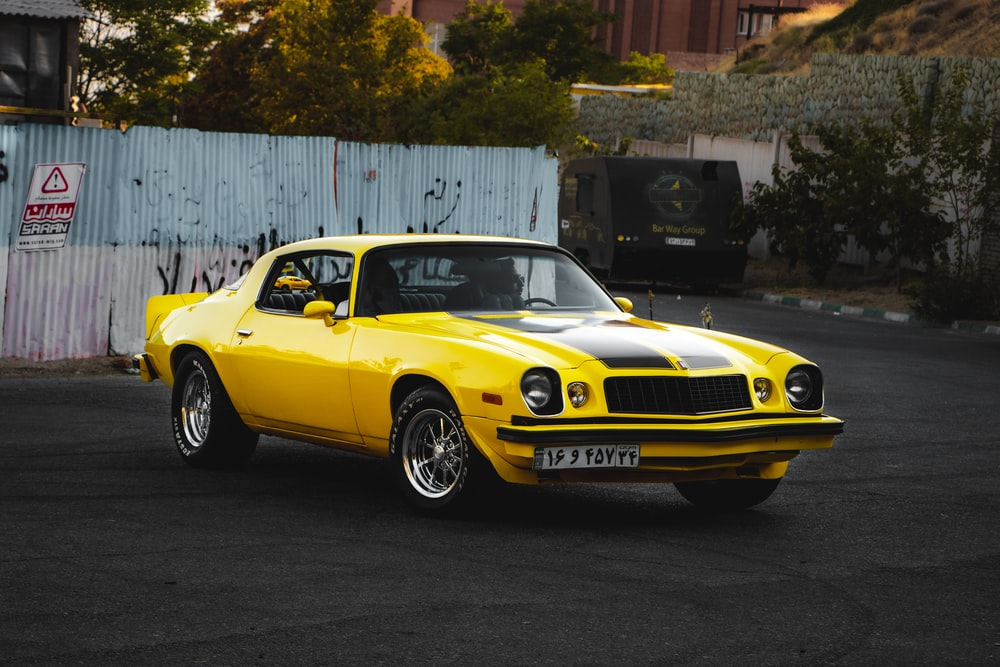 yellow chevrolet camaro parked beside white wall