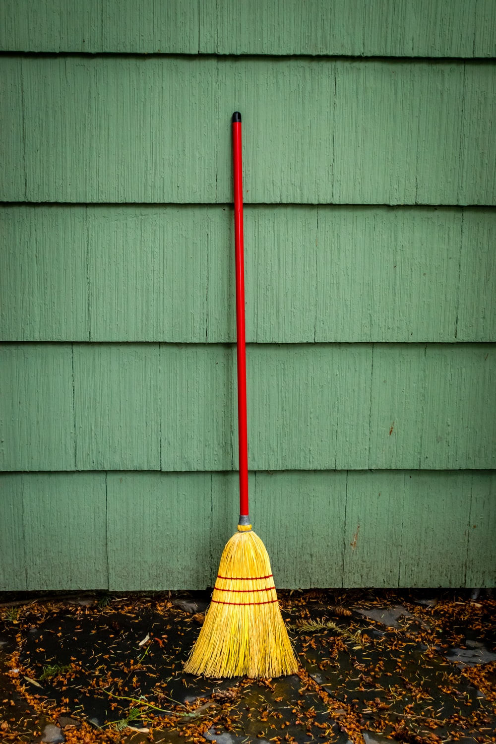 yellow broom leaning on white wall