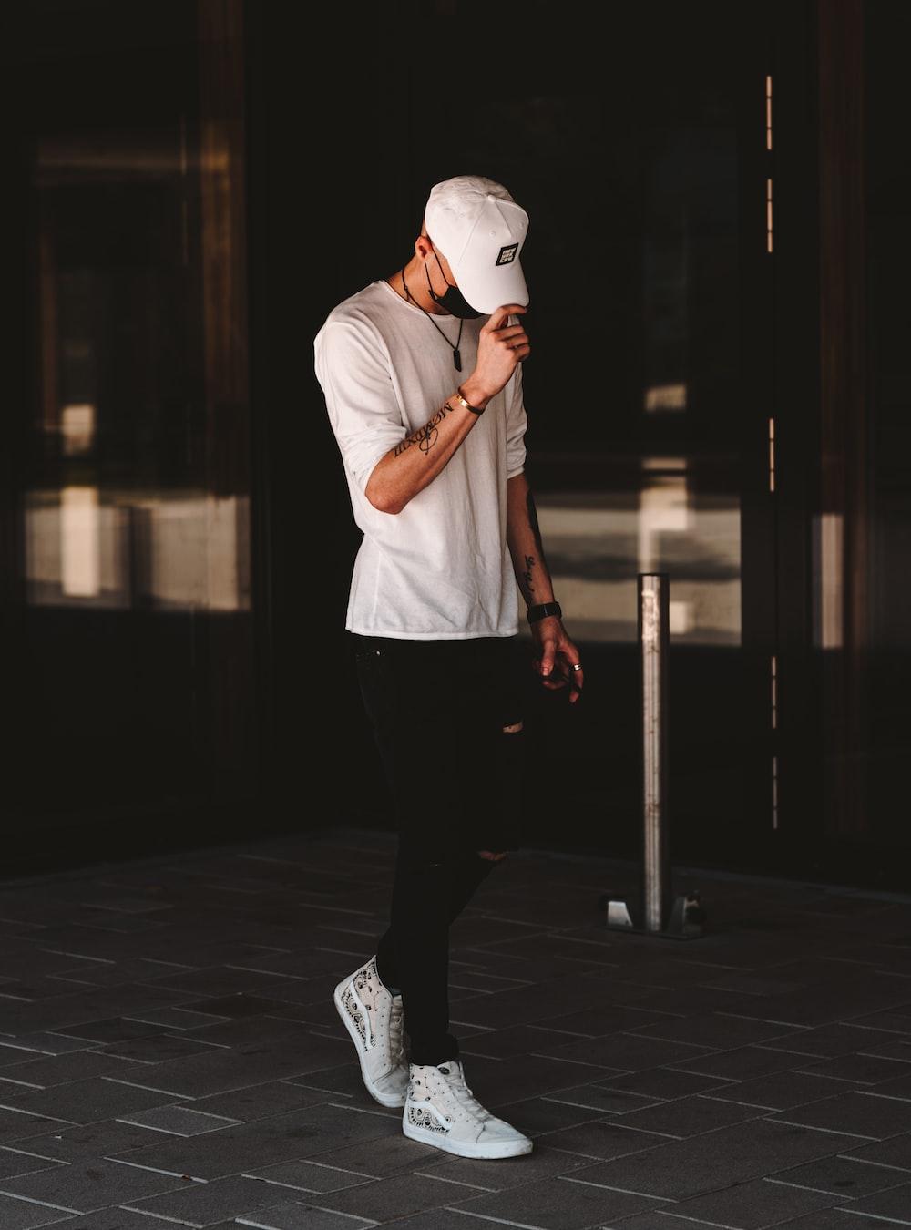 man in white t-shirt and black pants wearing white cap